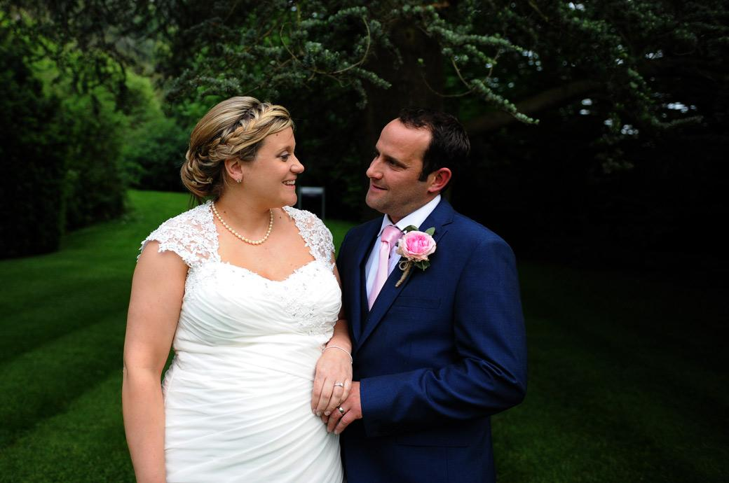 Bride and groom share a special tender moment in this wedding photograph far away from the madding crowd in the secluded lawn area at the Burford Bridge Hotel Surrey