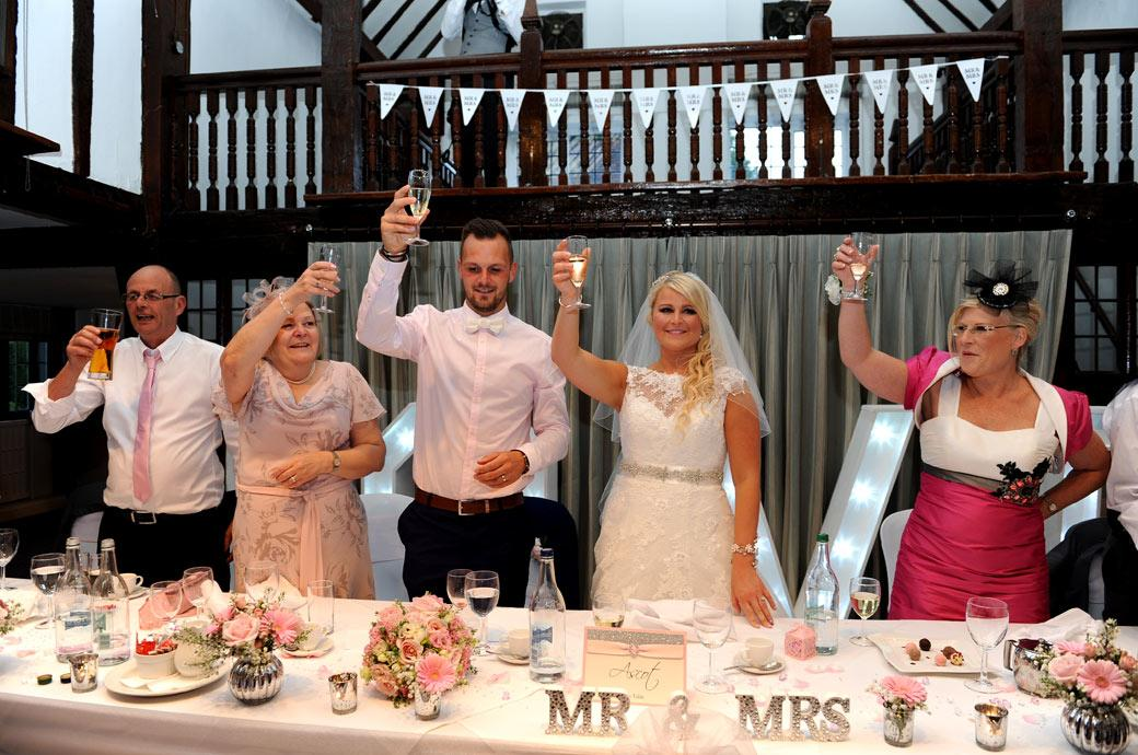 Bride and Groom on the top table raises their glasses for the final toast in The Tithe Barn at Surrey wedding venue Burford Bridge Hotel  during the wedding speeches