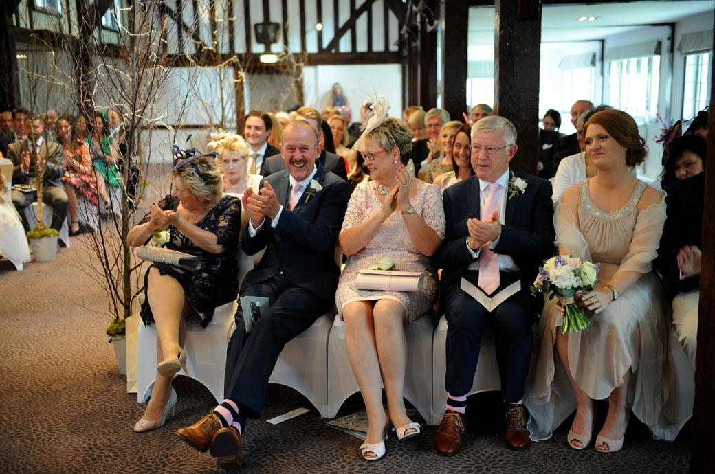 Happy and joyful wedding picture of the delighted parents applauding the marriage of their children in the Tithe Barn in Surrey at the Burford Bridge Hotel