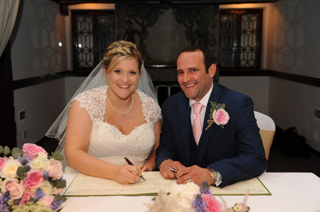 A relieved and delighted Bride and Groom sign the marriage register in this wedding photograph taken at the Burford Bridge Hotel near Box hill in Dorking Surrey