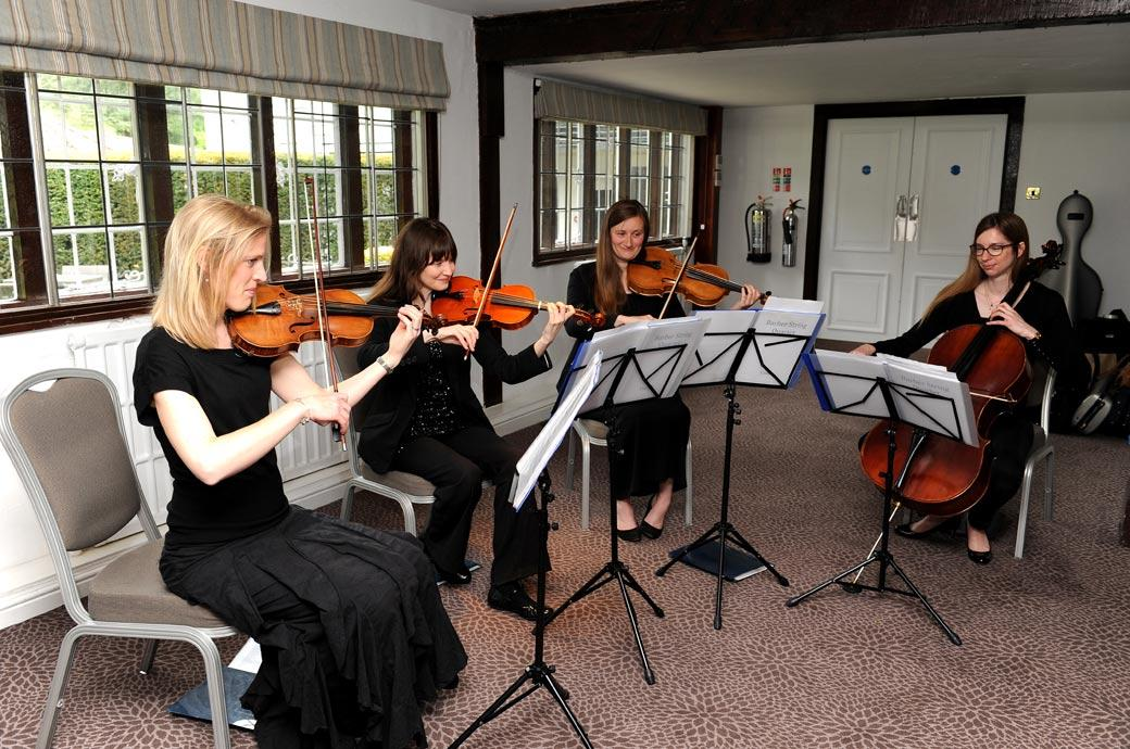All lady string quartet signal the arrival of the Bride in this wedding photo taken in Dorking Surrey in the Tithe Barn at the post flood newly refurbished Burford Bridge Hotel