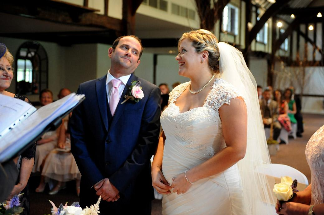 Intimate moment for the Bride and Groom as they eye each other in this wedding photo taken as they about to get married in the Tithe Barn at Burford Bridge Hotel in Surrey