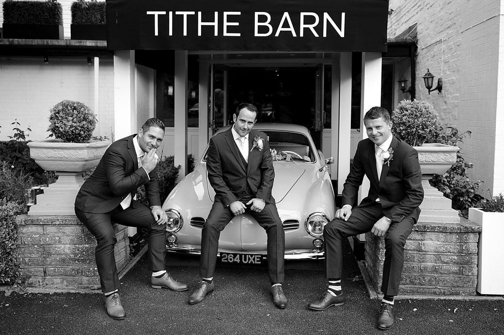 The Groom having fun as he sits on a classic car in front of the Tithe Barn at the Burford Bridge Hotel in Surrey and strikes a pose with his best men