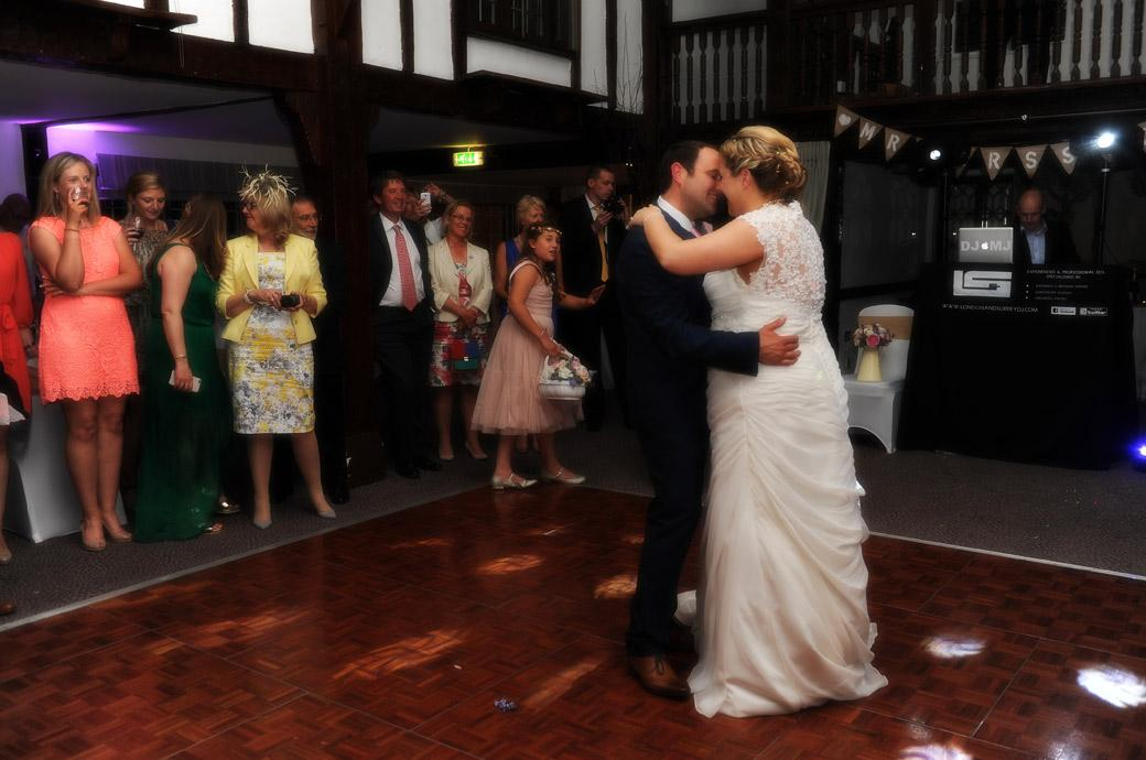 Bride and Groom enjoying an intimate moment as they take their first dance in this wedding photograph from the Tithe Barn in Surrey wedding venue the Burford Bridge Hotel