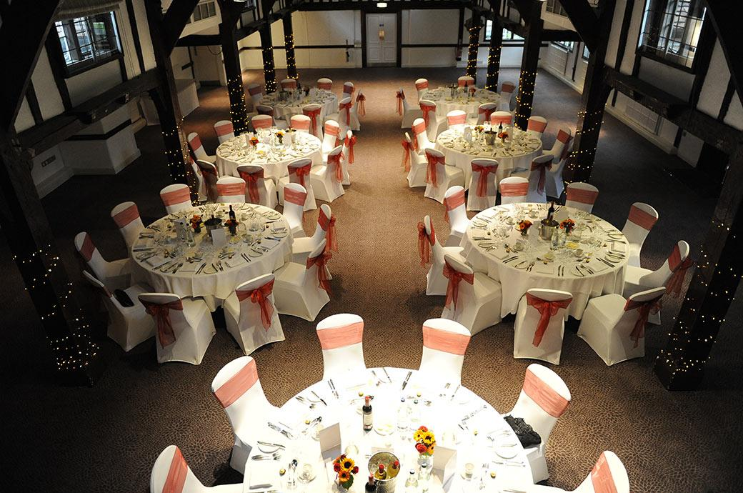 The Tithe Barn at Surrey wedding venue Burford Bridge Hotel in Dorking dressed ready for the wedding breakfast captured from the minstrel gallery