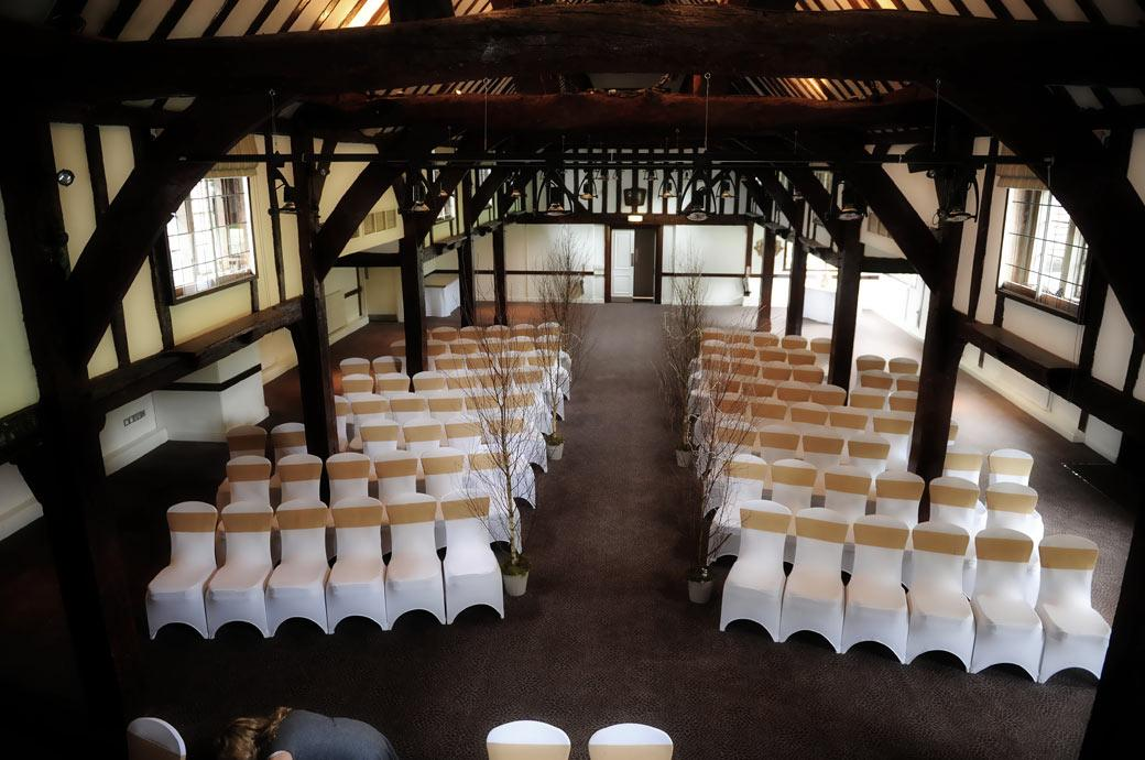 Inside the 16th century Tithe Barn ready for the marriage ceremony captured in this wedding picture taken at Surrey wedding venue Burford Bridge Hotel from the balcony