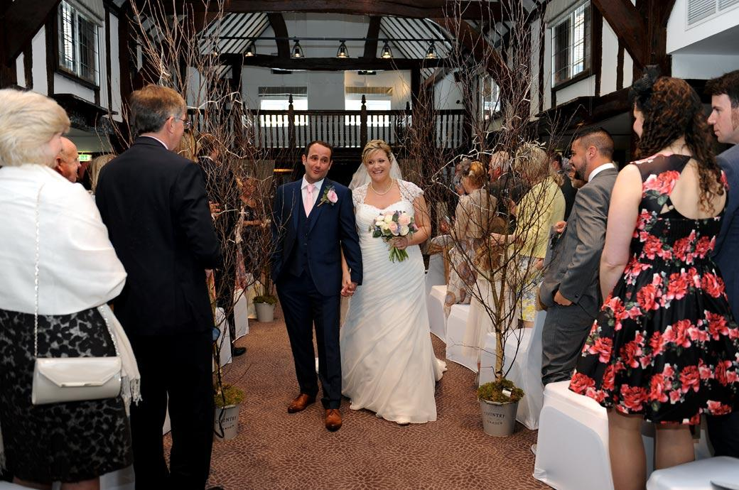 Happy Bride and Groom in The Tithe Barn at Surrey wedding venue Burford Bridge Hotel captured in this wedding photograph as they walk down the aisle a married couple