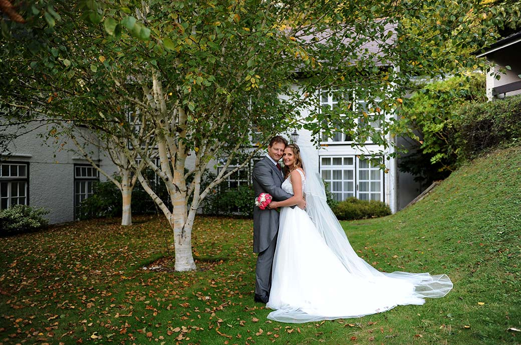 Romantic couple embracing wedding photograph taken on the tranquil lawn area of the popular wedding venue Burford Bridge Hotel in Dorking Surrey