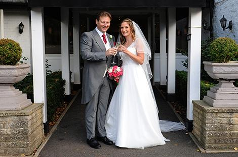 Happy Bride and groom toasting each other with a glass of champagne as they stand outside the Tithe Barn entrance to Surrey wedding venue Burford Bridge Hotel in Dorking