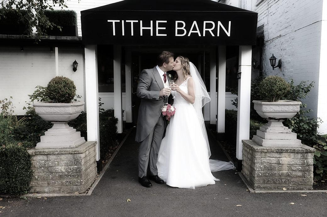 Bride and Groom captured at Surrey wedding venue Burford Bridge Hotel at the entrance to the Tithe Barn romantically kiss