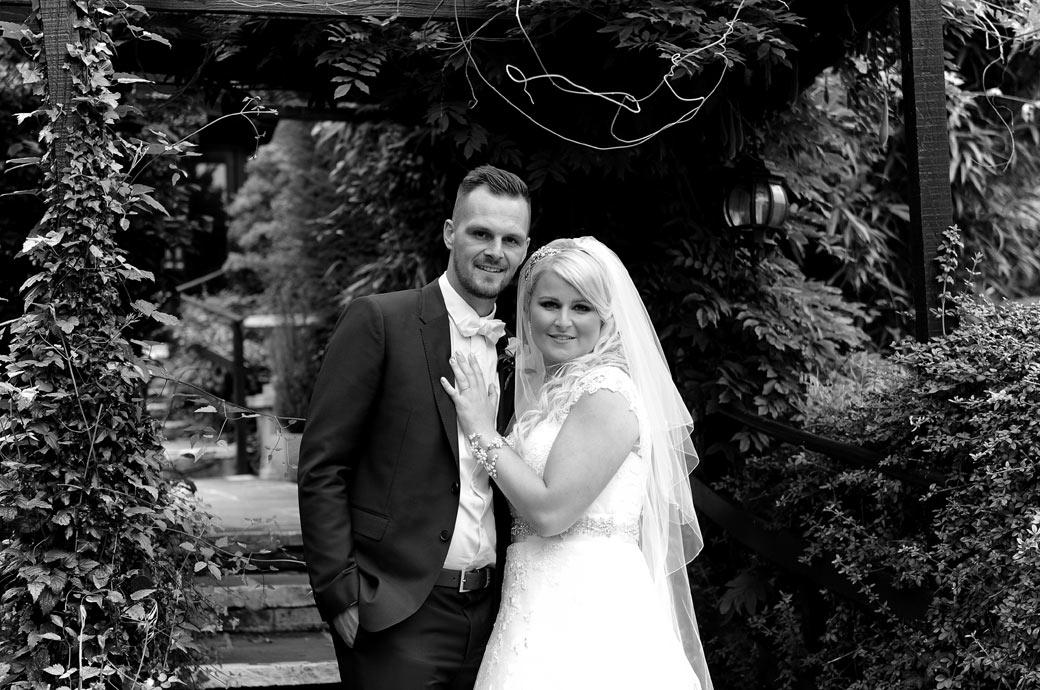 Relaxed smiling portrait wedding picture of the Bride and Groom standing together at Surrey wedding venue Burford Bridge Hotel in front of the colourful garden arbour