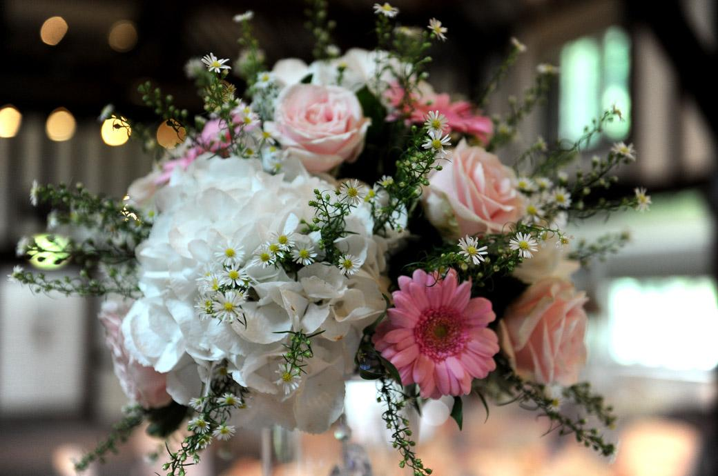 Beautiful table flower display wedding photograph taken from the wedding breakfast settings in Surrey at Burford Bridge Hotel in the ancient Tithe Barn