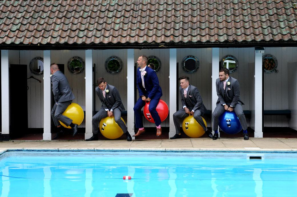 Out of the swimming pool changing cubicles on Space Hoppers in this funny and unusual wedding photograph from Burford Bridge Hotel a Surrey wedding venue in Dorking