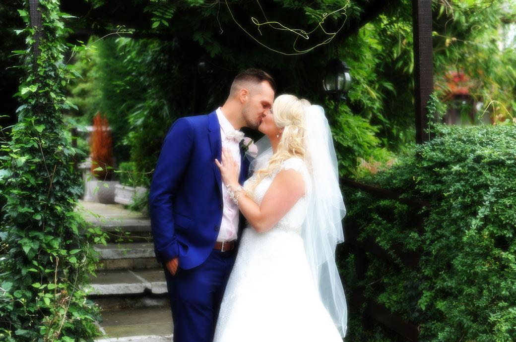 Romantic wedding picture of a Bride and groom kissing taken in the garden at Surrey wedding venue Burford Bridge Hotel by the arbour steps