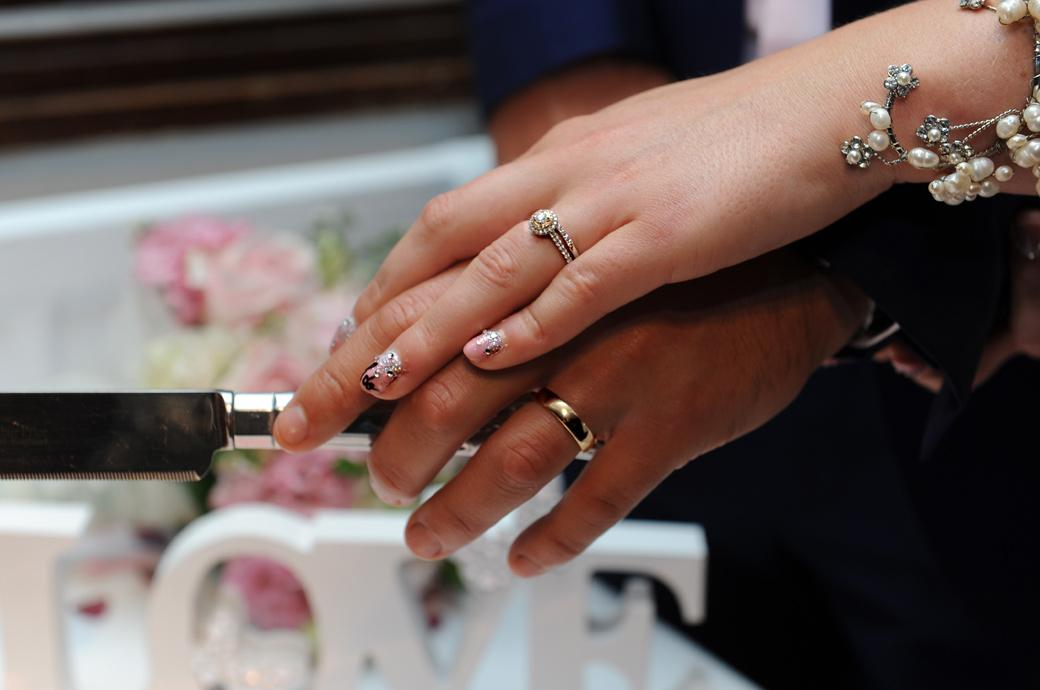 Pearls, gleaming wedding rings and sparkling nails captured in this cake cutting picture captured at Surrey wedding venue Burford Bridge Hotel in the historic Tithe Barn