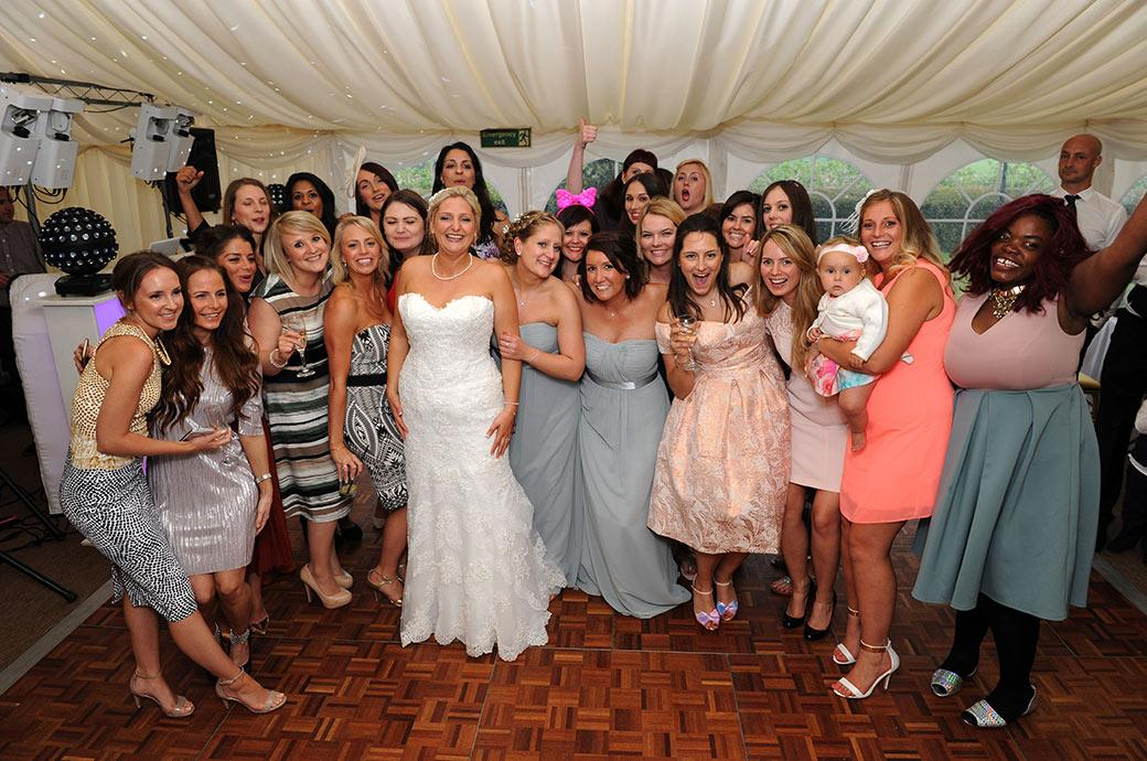 A beaming happy bride poses with her Hen night ladies for her Surrey Lane wedding photographer in the lively evening entertainments in the Burrows Lea Country House marquee