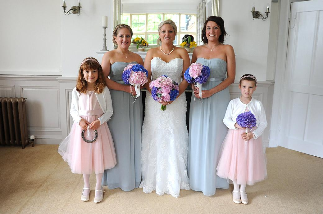 Bride and Bridesmaids lining up in front of the fireplace for an indoor group wedding photograph at Surrey wedding venue Burrows Lea Country House on a wet wedding day