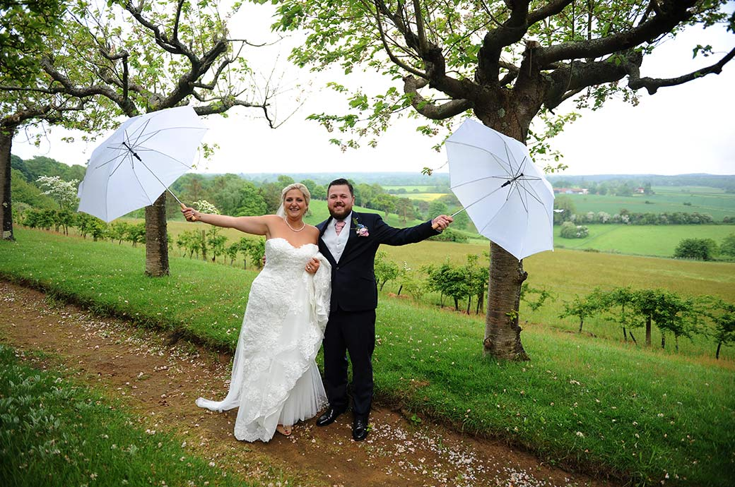 Beaming Burrows Lea Country House newlywed couple share their fun at this delightful Surrey wedding venue as they wave their umbrellas in the air as they rain stops