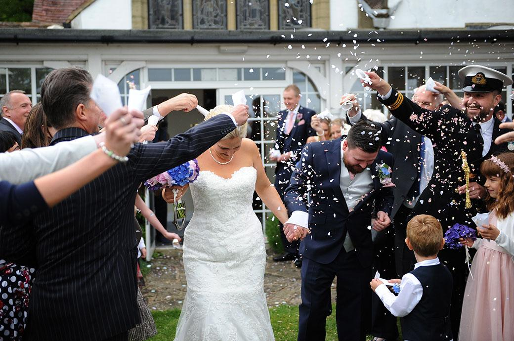 Bride and groom at Burrows Lea Country House in Shere village Surrey out on the lawn outside the chapel getting covered in wedding confetti by their guests