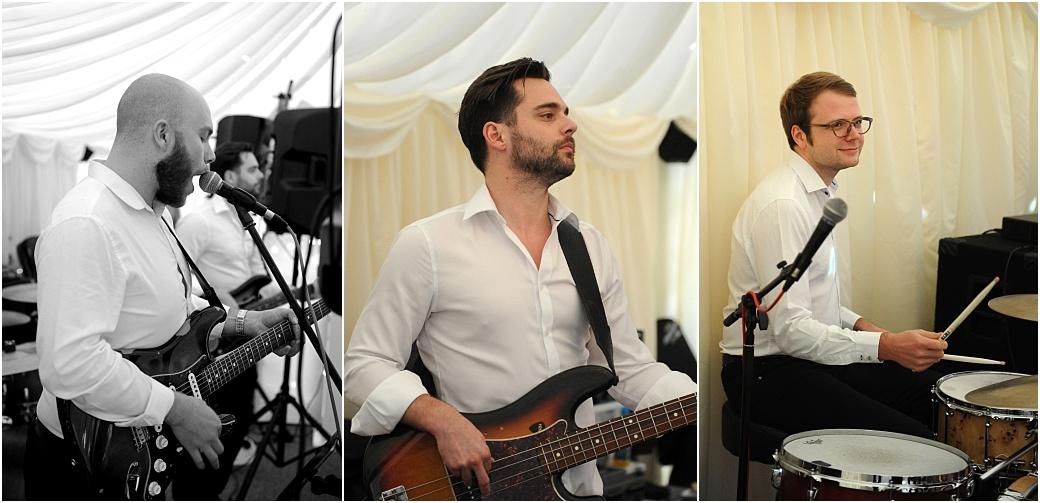 Guitarist, singer and drummer do their set during the evening celebrations in the marquee at Burrows Lea Country House a wonderful wedding venue in green and leafy Surrey