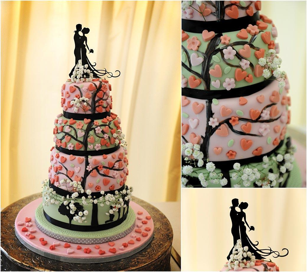 Four tier tree themed wedding cake in green and pink covered in love hearts and complete with a striking silhouette cake topper at Surrey venue Burrows Lea Country House