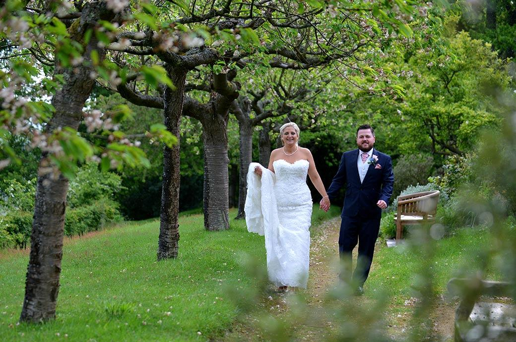 Romantic wedding picture of the happy newlywed couple at Burrows Lea Country House in Shere Surrey enjoying a walk along the Cherry Tree Walk hand in hand