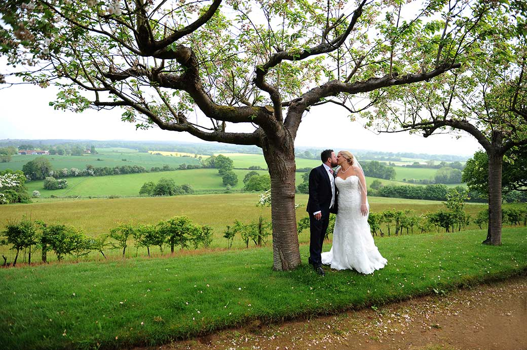 Beautiful views of the Surrey Hills captured on the delightful Cherry Tree Walk at Burrows Lea Country House wedding venue as a newlywed couple romantically kiss