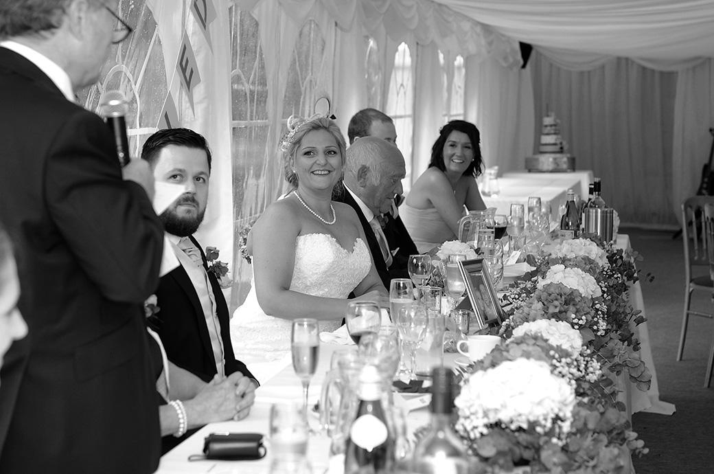 Wedding picture of a Bride smiling at her father during the wedding speeches in the marquee at Burrows Lea Country House  out in the beautiful green Surrey countryside
