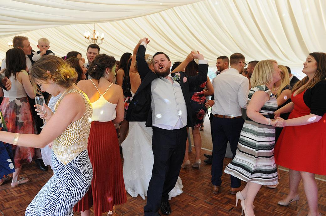 Happy Groom enjoying dancing with his wife and the other reception guests in the marquee at Burrows Lea Country House Surrey as the evening celebrations get into gear