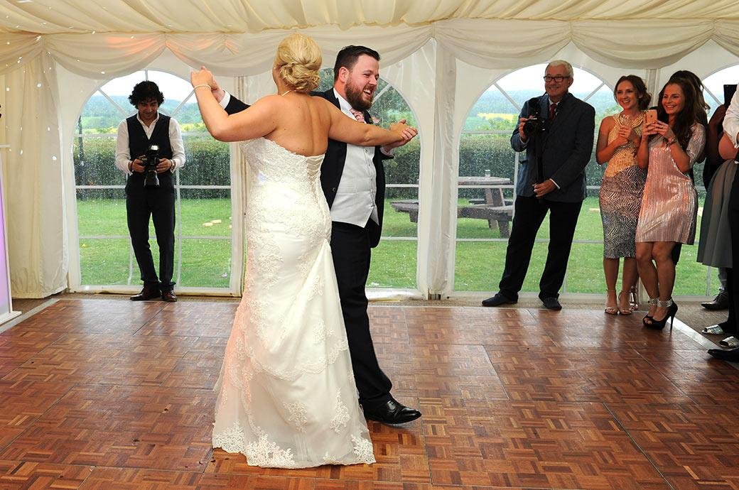 A happy Groom in the marquee at Burrows Lea Country House Surrey enjoying himself as he leads his wife on the dance floor for their first dance