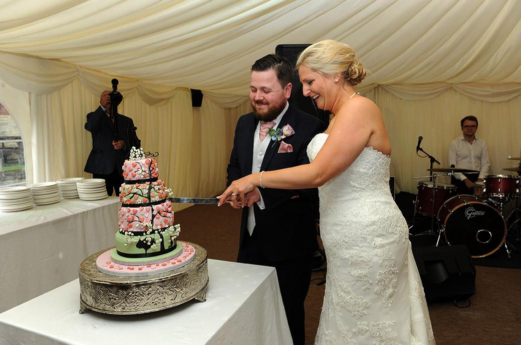Big and fun moment for the Bride and Groom as they cut their wedding cake in the marquee at the delightful Surrey wedding venue Burrows Lea Country House in Shere
