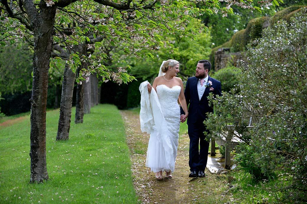 The beautiful Cherry Tree Walk at Burrows Lea Country House in Surrey makes a romantic setting for the newlywed couple as they talk and walk together hand and hand