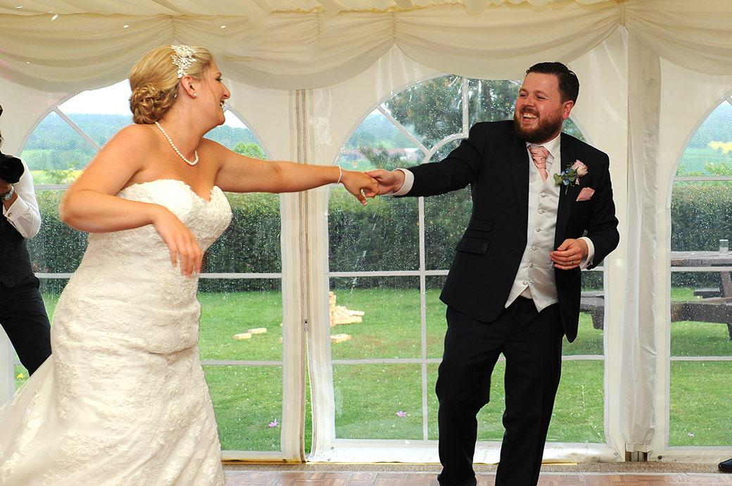 The laughing Bride and Groom complete a swinging move during their fabulous first dance at the lovely Burrows Lea Country House Surrey wedding venue