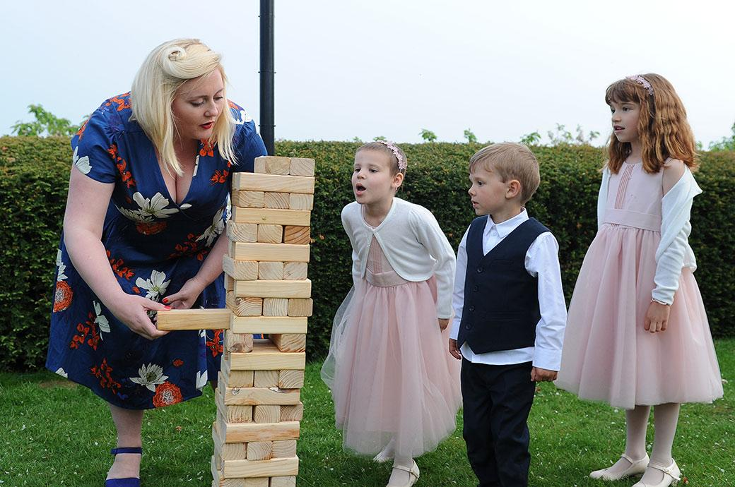 A caught in the moment wedding photograph on the lawn at Burrows Lea Country House Surrey of a bridesmaid blowing at the giant Jenga stack as a guest removes a brick