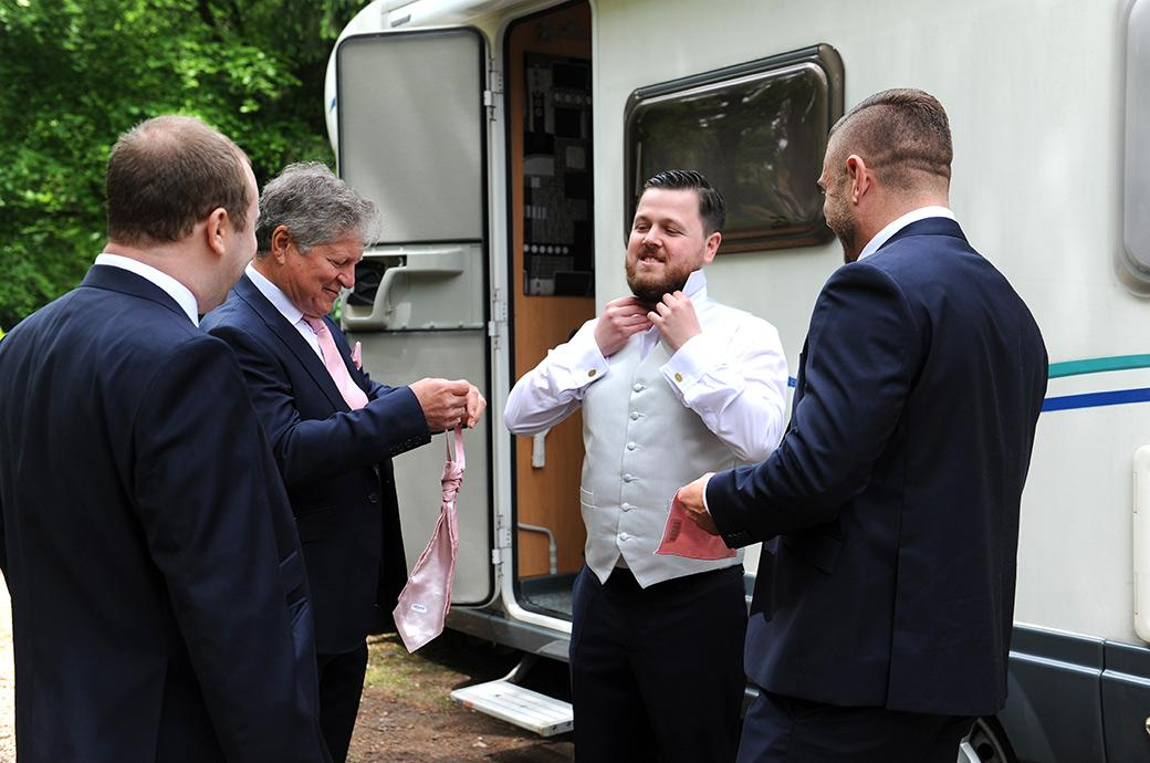 Smiling Groom being helped with his cravat as he makes the final touches for his marriage at the lovely and tranquil Surrey wedding venue Burrows Lea Country House in rural Shere  Surrey
