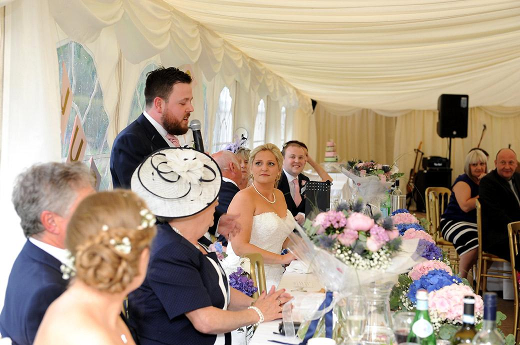An emotional Bride looks on as the Groom says some lovely words during his wedding speech at the green and tranquil Surrey wedding venue Burrows Lea Country House
