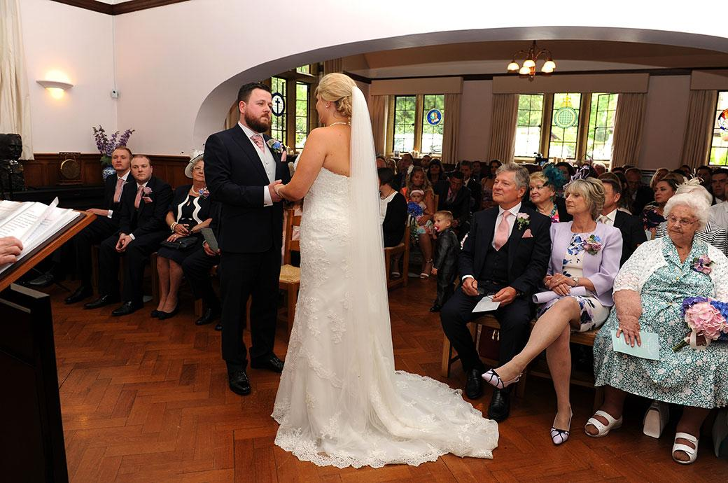 The proud Groom pictured here in the chapel at Surrey wedding venue Burrows Lea Country House holds his Bride's hands and looks on as she says her marriage vows