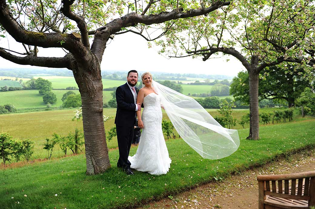Smiling Bride's veil blows in the wind as she stands with her husband on the scenic Cherry Tree Walk at Burrows Lea Country House a true gem of a Surrey wedding venue