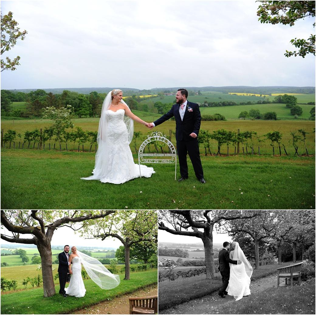 Handsome newlywed couple captured in these wedding photos as they walk and stand on the wonderful Cherry Tree Walk in Surrey at Burrows Lea Country House near Shere Village