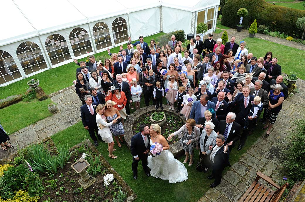 Wedding photo of the Bride and groom kissing as all the guests look up to the Surrey Lane wedding photographer during the everyone group shot at Burrows Lea Country House