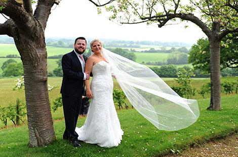 Beautiful wedding picture of the Bride and Groom standing in front of the stunning views from the Orchard Walk at Burrows Lea Country House a wedding venue in Shere Surrey