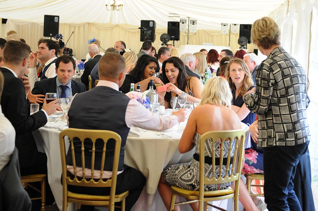 Candid wedding photograph of guests enjoying themselves during the wedding breakfast in Surrey wedding venue Burrows Lea Country House in the marquee