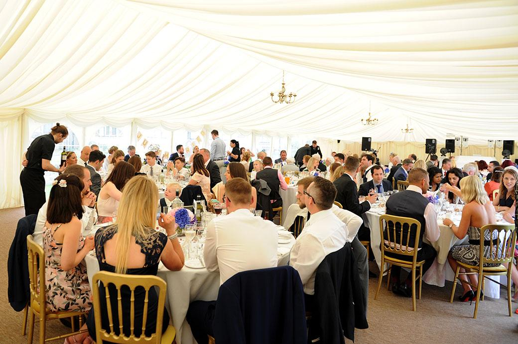Everyone seated in the large marquee at the rural Surrey wedding venue Burrows Lea Country House for the commencement of the wedding breakfast and afternoon celebrations