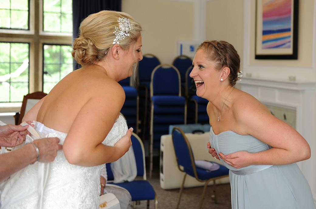 Wedding dress adjustment fun in this light hearted wedding picture taken as the Bride gets ready at Surrey wedding venue Burrows Lea Country House near the village of Shere