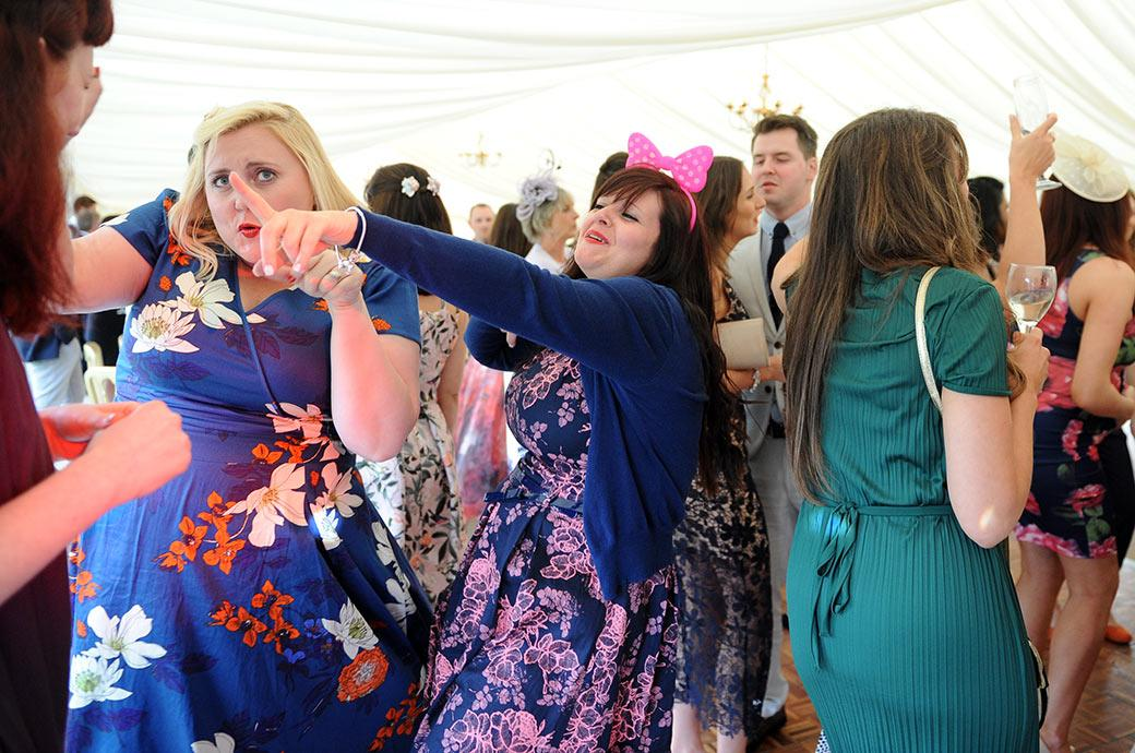 Bright colourful fun scene on the Burrows Lea Country House dance floor in Surrey as the wedding guests let down their hair and get into their moves