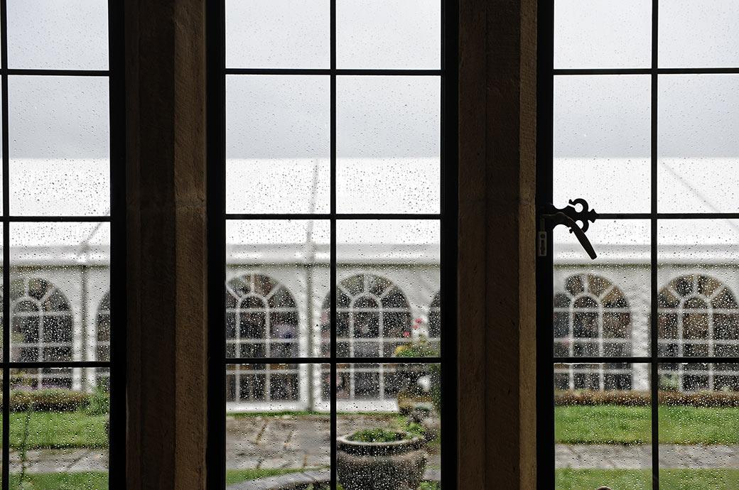 The Burrows Lea Country House marquee pictured through a rain covered window on a wet afternoon in the Surrey countryside during the wedding breakfast