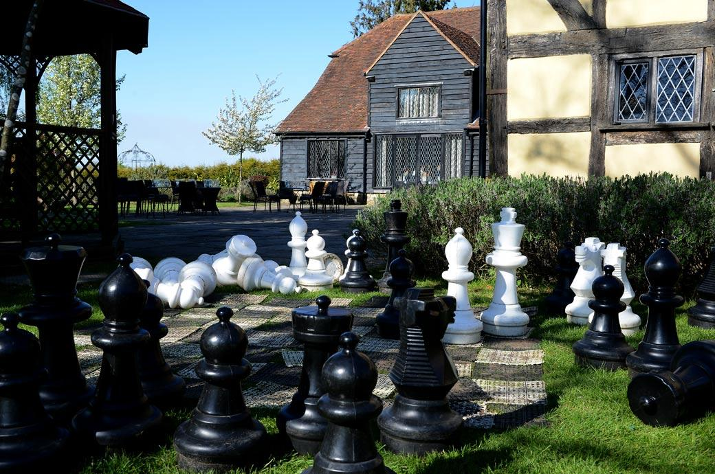 Fallen over and abandoned garden chess pieces captured in this wedding photo taken in the empty courtyard at Cain Manor in Surrey whilst everyone enjoys the wedding breakfast
