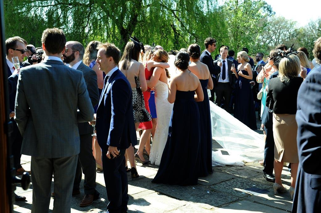 Bride receives a hug in a packed courtyard captured by a Surrey Lane wedding photographer at the Bijou hotel Cain Manor in the small village of Churt