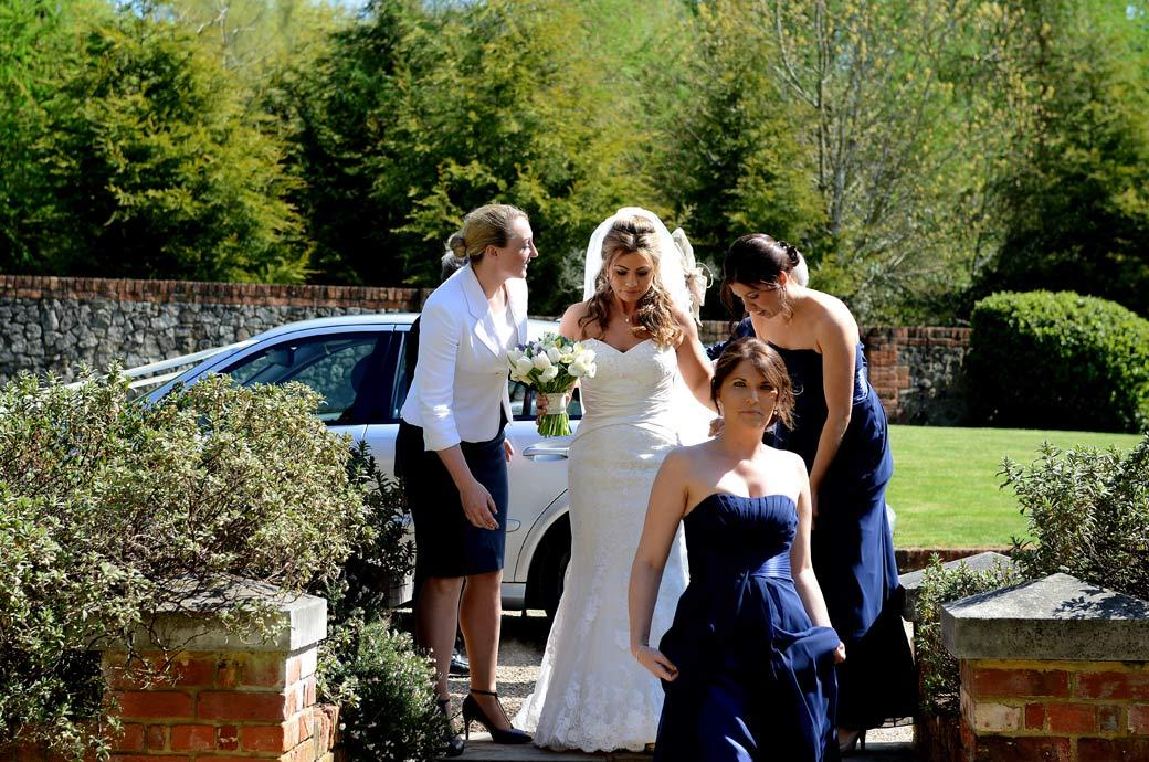 Bride captured here as she arrives at Cain Manor in Churt Surrey in this wedding photograph taken as she helped down the steps to the front door of this charming wedding venue