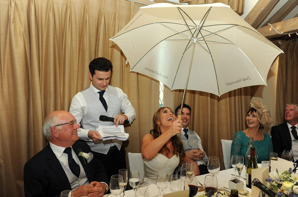 Bride receiving a special marriage umbrella during the best men's speeches captured in the Music Room at Cain Manor Churt in this unusual wedding photo